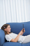 Little girl using digital tablet on the couch Stock Photo