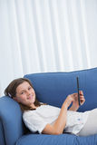 Little girl using digital tablet on the couch Royalty Free Stock Photography