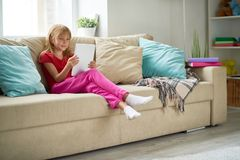 Little Girl Using Digital Tablet at Home. Portrait of blonde little girl using digital tablet and smiling happily while watching cartoons relaxing on big Stock Images