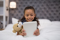 Little girl using digital tablet while lying on bed at home Royalty Free Stock Image
