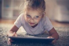 Little girl using digital tablet. stock image
