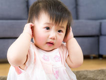 Little girl using hand to cover ear Royalty Free Stock Image