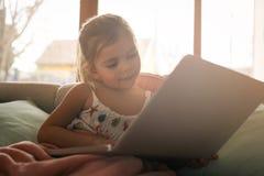 Little girl using her laptop. Stock Images