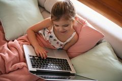 Little girl using her laptop. Little blonde girl using laptop and sitting on couch. From above Royalty Free Stock Photo