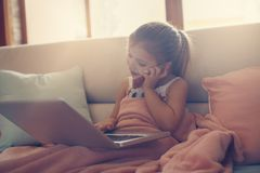 Little girl using her laptop. Little blonde girl using laptop and smart phone at home Royalty Free Stock Photo