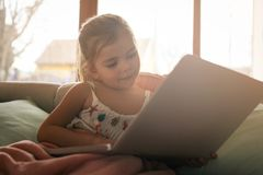 Little girl using her laptop. Little blonde girl using laptop and sitting on couch. Little girl at home Stock Photo