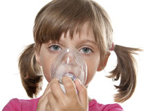 Little girl using inhaler. Ill little girl using inhaler - respiratory problems white background Royalty Free Stock Photo
