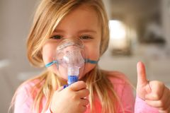 Little girl using inhaler. Little girl using inhaler and showing OK. Looking at camera. Close up image of little girl stock photo