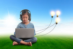 Little girl using a laptop with creative light bulb ideas Royalty Free Stock Photography