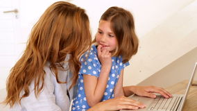 Little girl using laptop with her mother at the table Royalty Free Stock Photos
