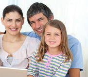 Little girl using a laptop with her parents Stock Photography