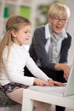 Little girl using laptop surprised grandma looking Stock Photography