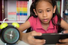 Little girl using mobile phone at home. Stock Photo