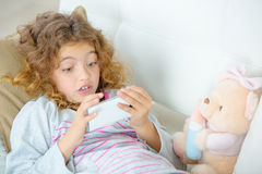 Little girl using mobile phone on sofa Royalty Free Stock Images