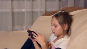 Little girl using modern smartphone sitting in soft chair at home. Young girl sitting in comfortable chair next window and looking at screen mobile phone stock footage
