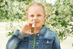 Free Little Girl Using Nasal Drops Near Blooming Tree. Allergy Concept Stock Photos - 150109763