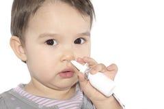 Little girl using nasal spray. White background Stock Image