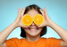 Little girl using oranges as glasses Stock Photo