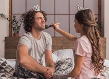Dad and daughter. Little girl is using a powder brush on her handsome dad who is smiling while they are playing together at home stock images