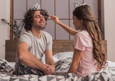 Dad and daughter. Little girl is using a powder brush on her handsome dad who is smiling while they are playing together at home royalty free stock photo