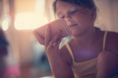 Dependency. Little girl using smart phone. Copy space. Close up. Focus on hand royalty free stock photography