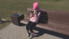 Little girl using smartphone. In summer day stock footage