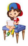 Little girl using tablet on a chair Royalty Free Stock Photography