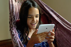Little girl using a tablet in a hammock Stock Photo