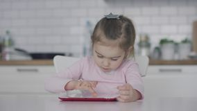 Little girl using tablet in kitchen stock video footage