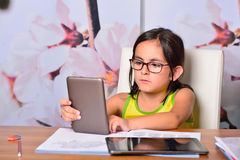 Little girl using a Tablet PC and an Ebook for homework Stock Photography