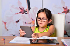 Little girl using a Tablet PC and an Ebook for homework Royalty Free Stock Photos