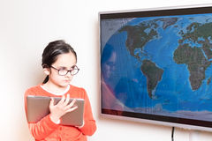Little girl using a Tablet PC and an interactive television for homework Royalty Free Stock Photography