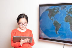 Little girl using a Tablet PC and an interactive television for homework. Little cute girl using at home a Tablet PC and an interactive television for homework Royalty Free Stock Photos