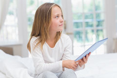 Little girl using tablet pc sitting on her bed Stock Photo