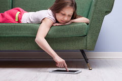 Little girl using a tablet relaxed on a sofa Stock Photos