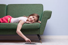 Little girl using a tablet relaxed on a sofa Royalty Free Stock Photo
