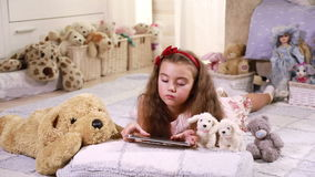 Little girl using touchpad. Cute little girl lying on the floor using touchpad in a living room stock footage