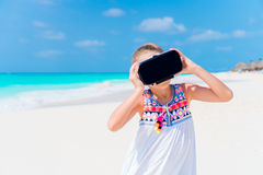 Little girl using VR virtual reality goggles. Adorable kid look into the virtual glasses on white beach Stock Photography