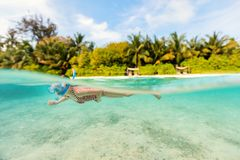Little girl on vacation. Split underwater photo of a little girl swimming in tropical ocean Royalty Free Stock Images