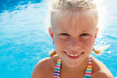 Little girl vacationers beside swimming pool in a. Portrait of a little girl vacationers beside swimming pool in a sunny summer day Stock Photo