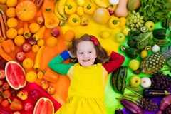 Healthy fruit and vegetable nutrition for kids. Little girl with variety of fruit and vegetable. Colorful rainbow of raw fresh fruits and vegetables. Child stock image