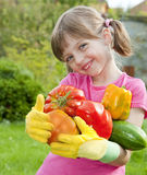 Little girl with vegetables Stock Images
