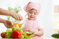 Little girl with vegetables on kitchen Royalty Free Stock Photo