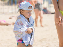 The little girl is very cold bathing in the sea and basking wrapped in a towel. Frozen four-year girl wrapped in a towel standing on the sandy beach sea stock image