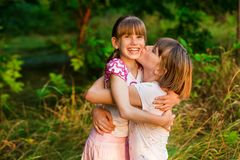 Little girl is very happy that she has sister. Loving sister hugging cute little girl showing love care support. Sincere warm relationships. Concept of happy royalty free stock photography