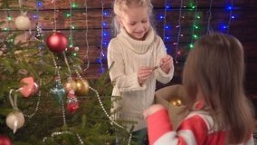 Two girls decorate a Christmas tree and talk. Little Girl Very Happy with her Christmas Present by the Christmas Tree stock video footage