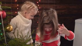 Two girls decorate a Christmas tree and talk. Little Girl Very Happy with her Christmas Present by the Christmas Tree stock footage