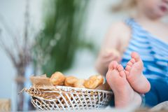 A little girl in a vest with a vest sits on the table. Focus on children`s legs. And a basket with croissants Stock Images