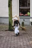 Little girl in Victorian costume dress sweeps the street with a. Deventer, The Netherlands, December 21, 2014: Little girl in Victorian costume dress sweeps the stock photography