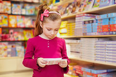 Little girl views envelopes in book department Royalty Free Stock Images